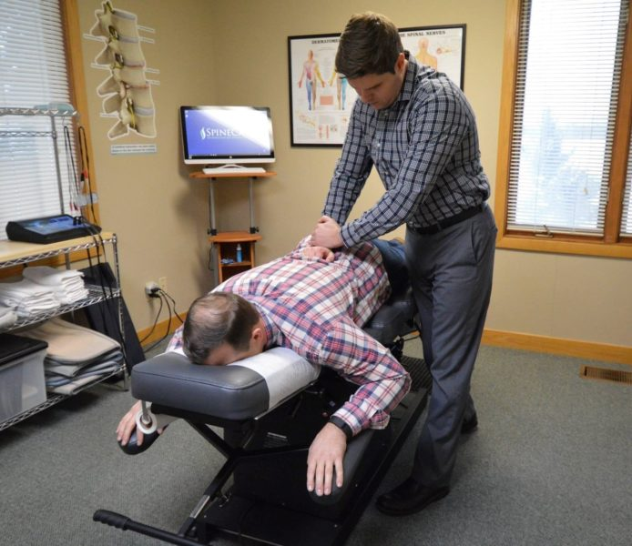 Dr. Rowe giving back pain chiropractic adjustment